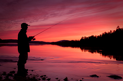 a silhouette of a man standing on a dock fishing under a bright red orange sky.
