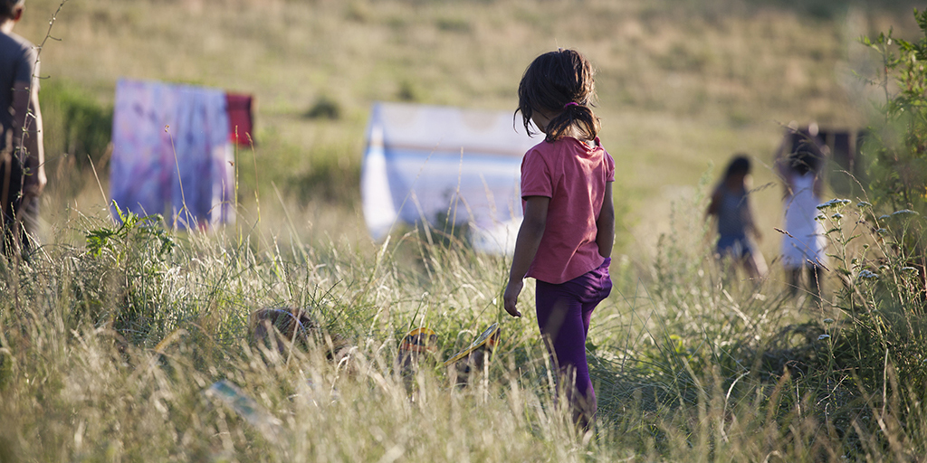 the back of a little girl with a pink shirt walking in the grassy fields lonely.