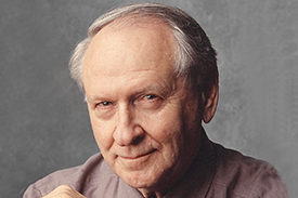William Safire smiling with a light maroon button down shirt on.
