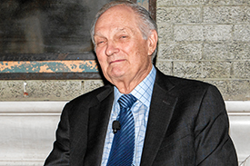 alda sitting with a royal blue tie, light blue collared shirt and suit jacket.