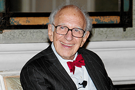 Eric R Kandel, sitting looking to the side, smiling with a red bow tie, white shirt and black coat.