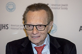 Larry King with a black sports coat and red bow tie.